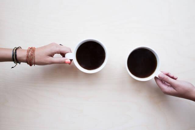 Hände und Kaffeetassen
